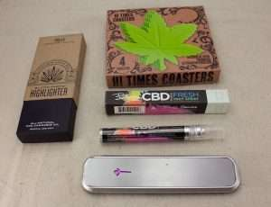L to R: Bloom Farms Indica Vape Pen, Gama Hi-Times Coasters, Bhang CBD Breath Spray, Genius Pipe